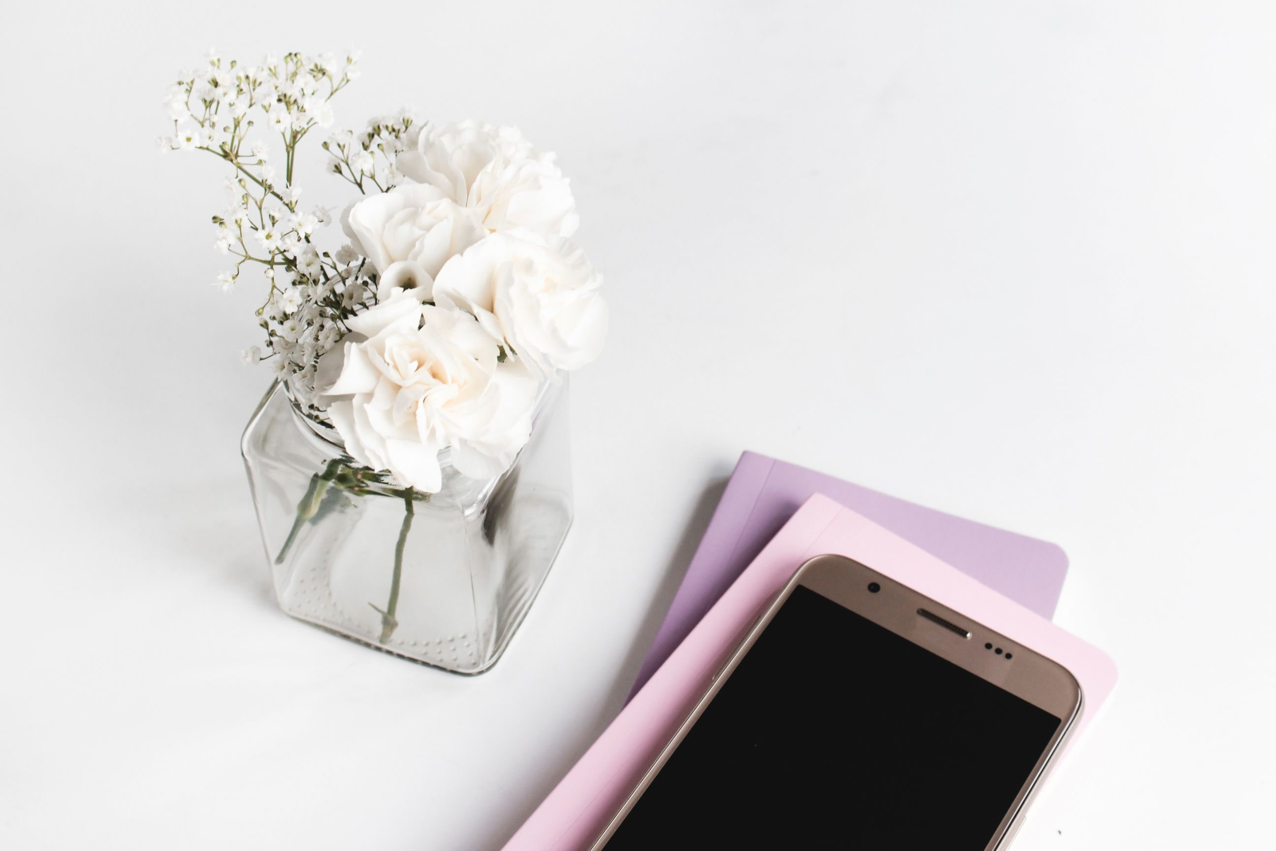 cell phone and flowers on home office desk