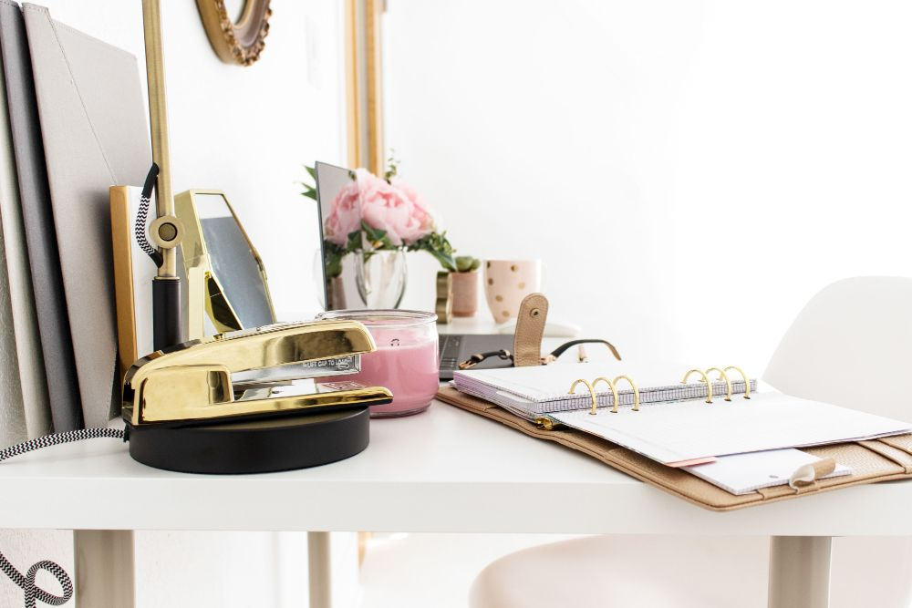 home office with planner and gold stapler on desk