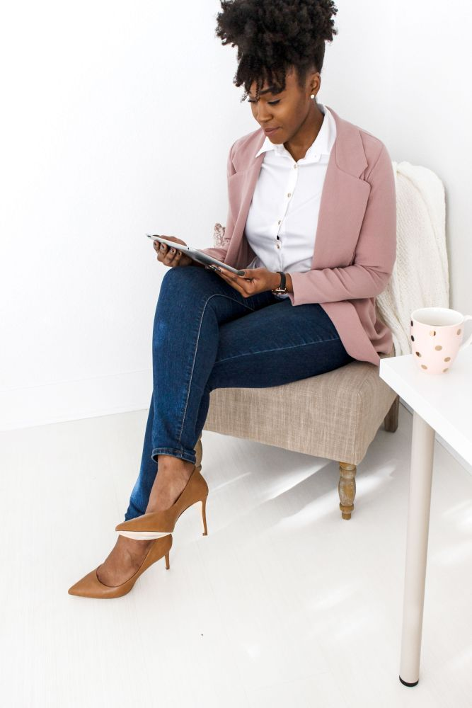 woman in pink blazer and jeans looking at ipad