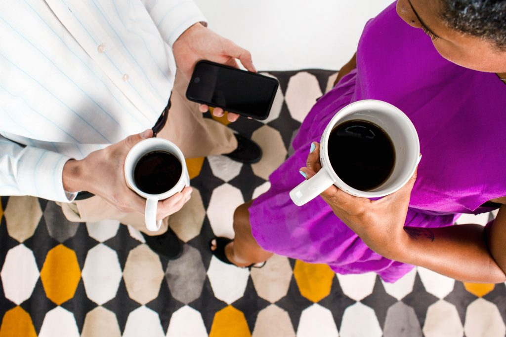 two people holding coffee mugs and phones