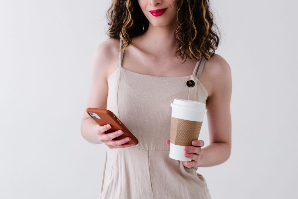 woman holding cell phone and cofee